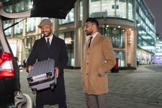 Businessmen loading suitcase into car on urban street corner at night
