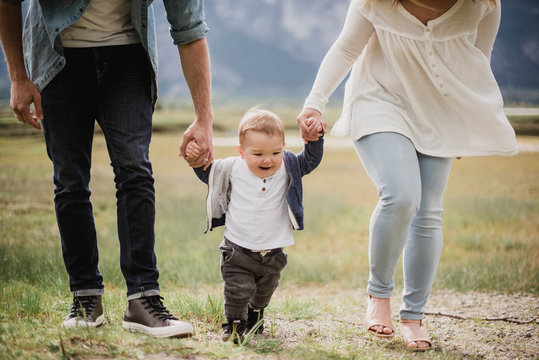 Parents walking with baby son in field