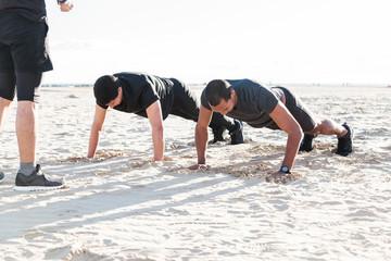Men doing push-ups on sunny beach