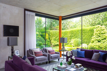 Modern living room with purple furniture and view of sunny garden