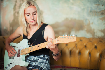 Young woman playing electric guitar on sofa