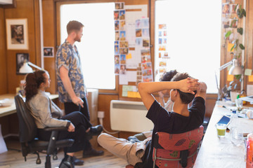 Creative designers brainstorming, reviewing photograph proofs in office