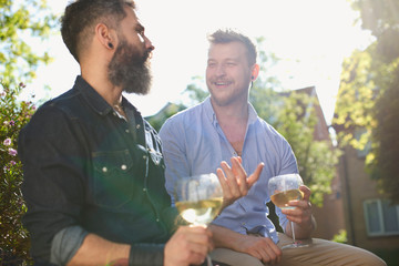 Smiling male gay couple drinking white wine in sunny garden
