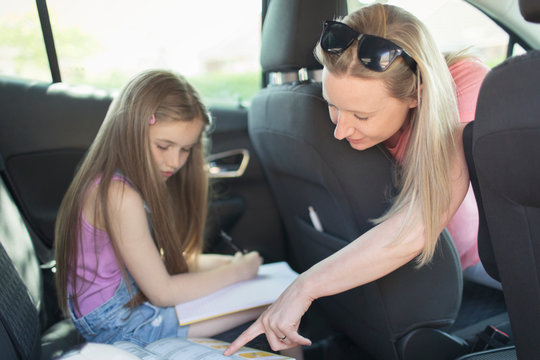 Mother helping daughter doing homework in back seat of car