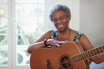 Portrait smiling, confident active senior woman playing guitar