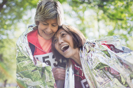 Happy active senior women friends hugging after sports race, wrapped in thermal blanket