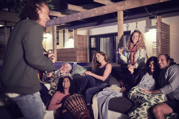 Happy friends hanging out, playing music on patio at night