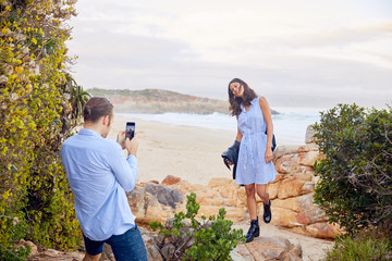 Young man with smart phone photographing girlfriend with ocean  Wall mural
