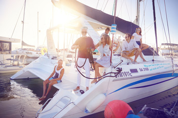 Friends relaxing on catamaran ins sunny harbor