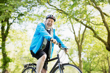 Portrait smiling active senior man riding bike in park