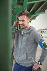 Young male runner with mp3 player arm band and headphones