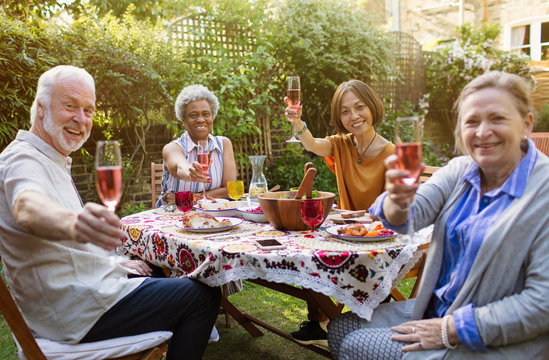 Portrait smiling, confident active senior friends drinking rose wine enjoying lunch at patio table