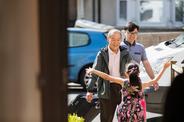Girl running to greet grandfather and father in sunny front yard