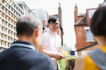 Happy man serving tea and juice to family in sunny yard