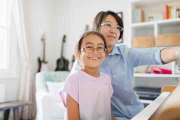 Mother and daughter playing piano Fotomurales