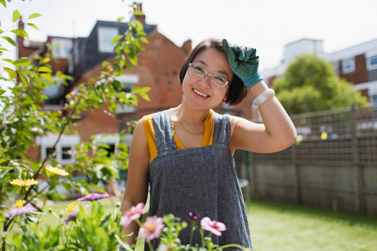 Portrait smiling woman gardening in sunny yard