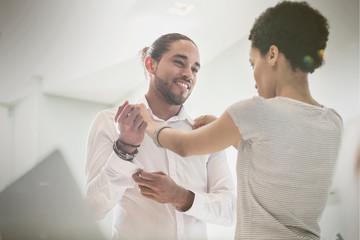 Woman helping boyfriend getting dressed, adjusting shirt collar
