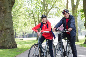 Portrait smiling, confident active senior couple riding bikes in park