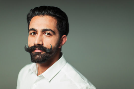 Portrait confident young man with handlebar mustache