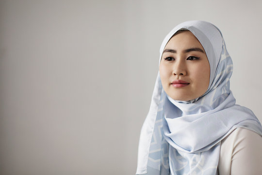 Portrait serene young woman in blue silk hijab looking away