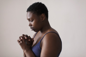 Portrait serene woman with rosary praying