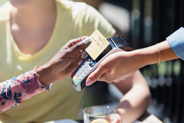 Woman paying waitress with smart card