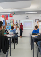 Female teacher in hijab answering student questions in classroom