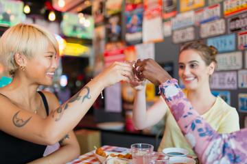 Young women friends taking alcohol shots in bar