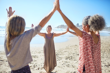 Women joining hands in circle on sunny beach during yoga retreat