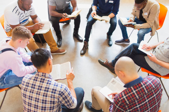 Men reading and discussing bible in prayer group