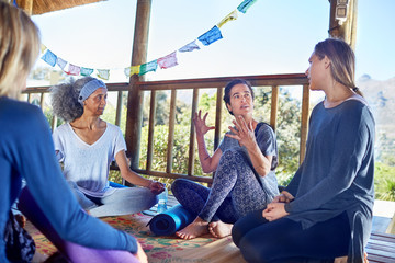 Women talking in hut during yoga retreat