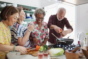 Active senior friends cooking in kitchen