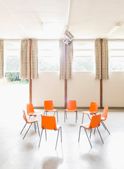 Orange chairs arranged in circle in community center