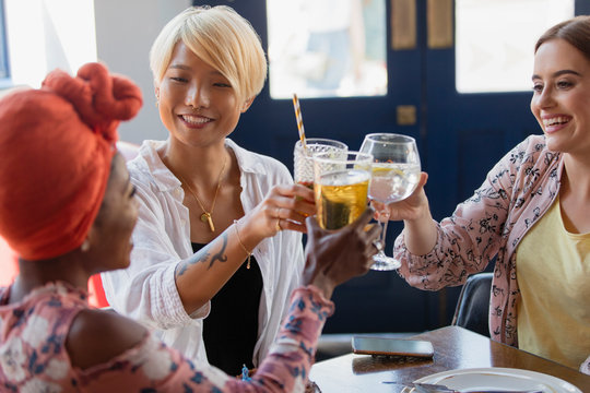 Young women friends toasting cocktail glasses in bar