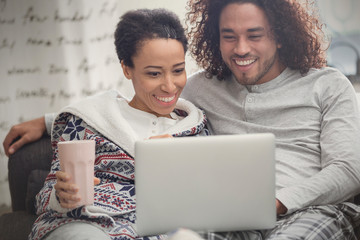 Happy couple in pajamas relaxing, using laptop on sofa