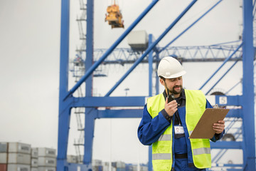 Dock worker with walkie-talkie and clipboard at shipyard