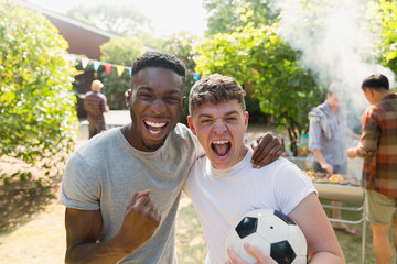 Portrait enthusiastic young men soccer ball cheering, enjoying back yard barbecue