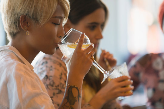Young woman drinking cocktail in bar
