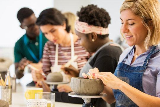Woman making clay bowl in art class