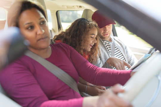 Family with map in car on road trip