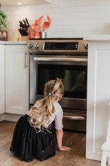 Curious girl watching oven