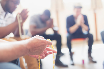 Men praying with rosaries in prayer group