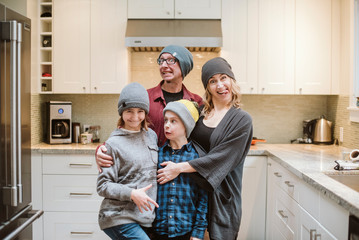 Portrait silly family making faces in kitchen