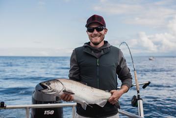 Portrait confident male fisherman catching fish