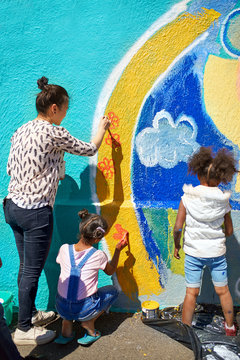Mother and daughter volunteers painting vibrant mural on sunny wall