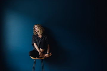 Portrait carefree woman sitting on stool against blue background
