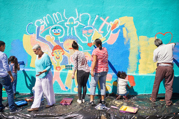 Community volunteers painting vibrant mural on sunny wall