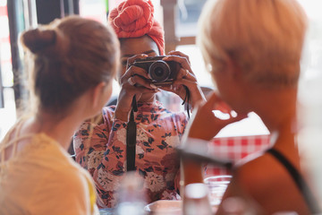 Young woman photographing friends with camera in restaurant