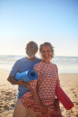 Portrait happy senior couple with yoga mats on sunny beach