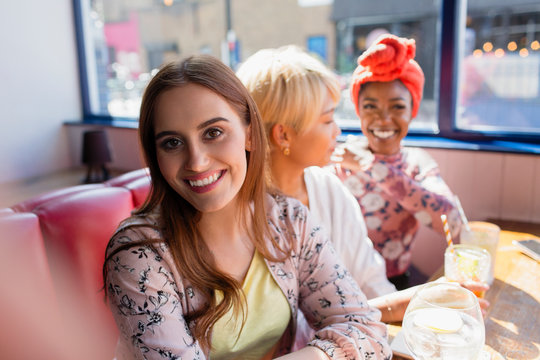 Portrait smiling young woman in sunny restaurant with friends
